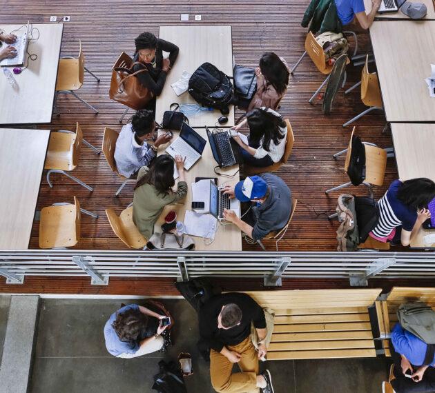 header étudiants travailant en open space sur ordinateurs