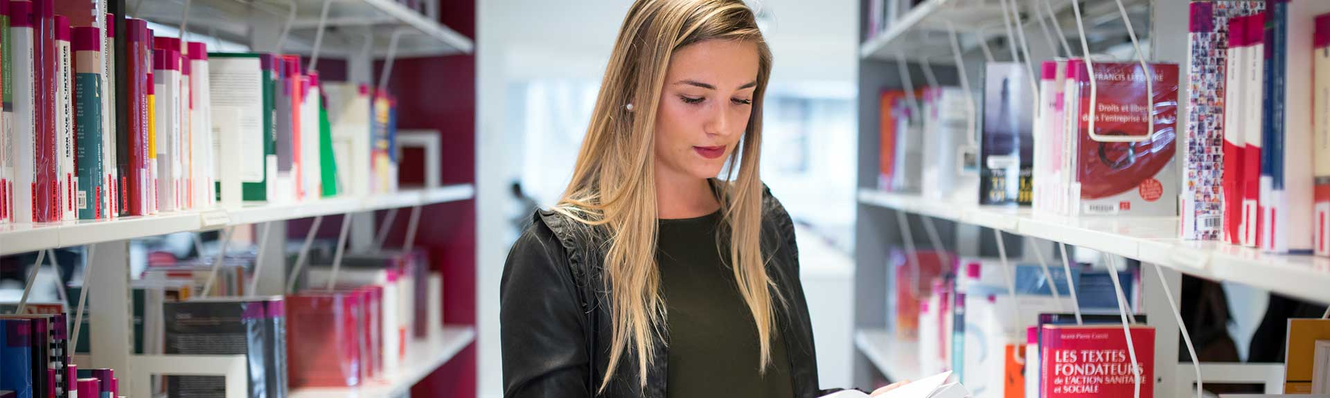 Une étudiante à la bibliothèque lisant un livre