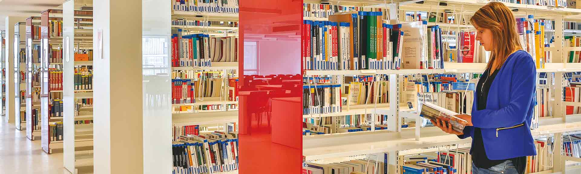 Une étudiante en train de lire un livre à la bibliothèque