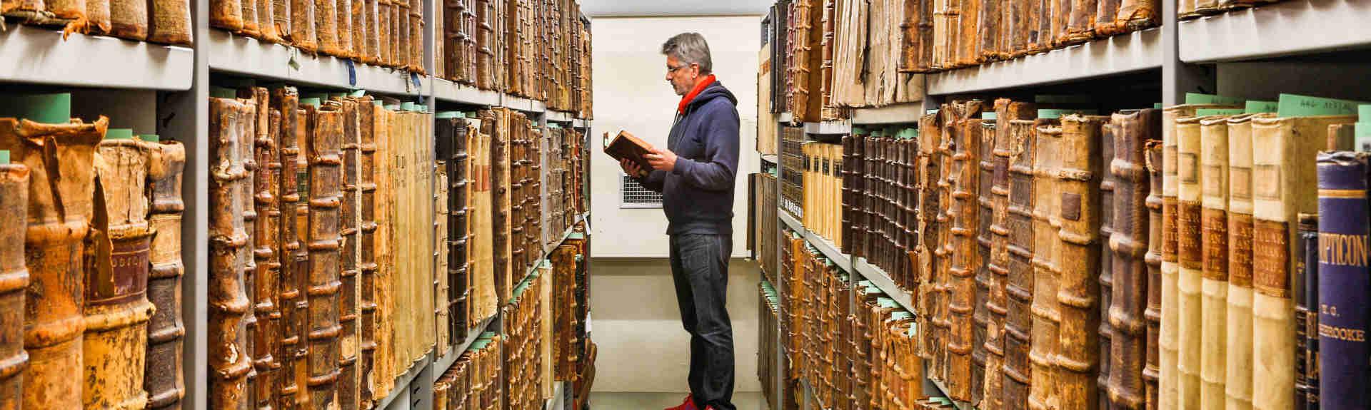 Header homme feuilletant un livre dans une bibliothèque de livres anciens