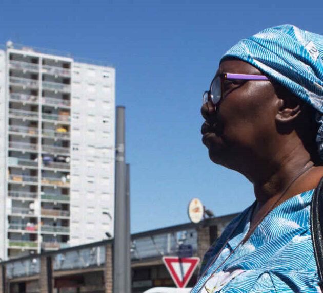 Header de ReliMig - Femme à un carrefour de ville en Afrique + logo ANR incrusté