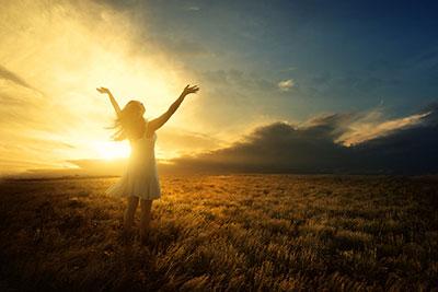 femme de dos devant coucher de soleil
