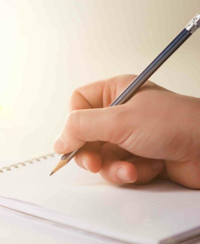 Une main d'homme avec un crayon qui écrit sur un bloc note